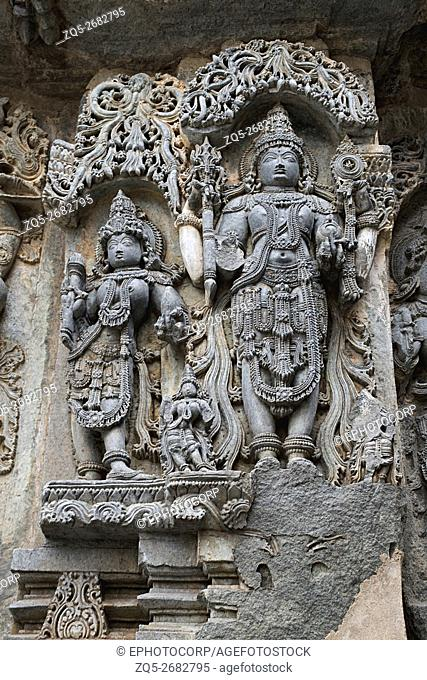 Ornate wall panel reliefs depicting (from left) Goddess Lakshmi; the wife of Vishnu, and Vishnu, Kedareshwara temple, Halebidu, Karnataka, india