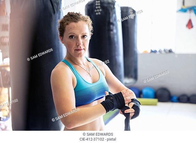 Portrait confident, tough female boxer wrapping wrists next to punching bags in gym