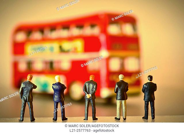Concept, business men waiting for a red bus from London. Figurines of businessmen watching a blurred red bus from London