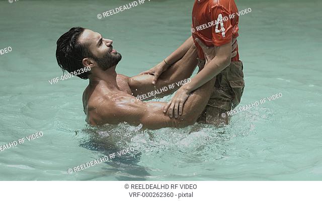 Man throwing his son while enjoying in swimming pool