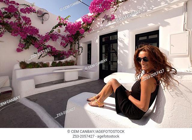 Woman sitting in a cafe, Mykonos, Cyclades Islands, Greek Islands, Greece, Europe