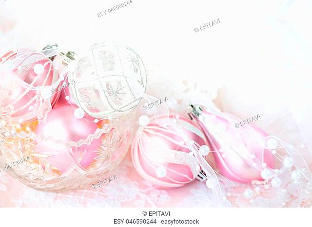 Beautiful Christmas decoration in white and pink colors: several Christmas balls with white ribbon and pearls on a light background, with space for text