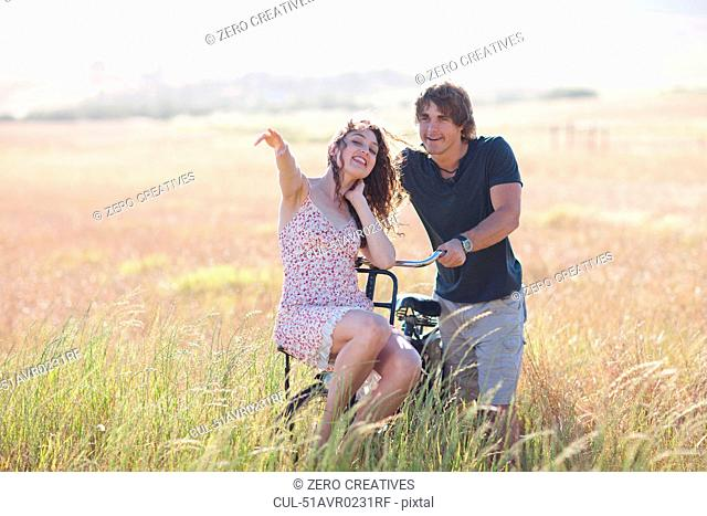 Couple playing on bicycle in tall grass