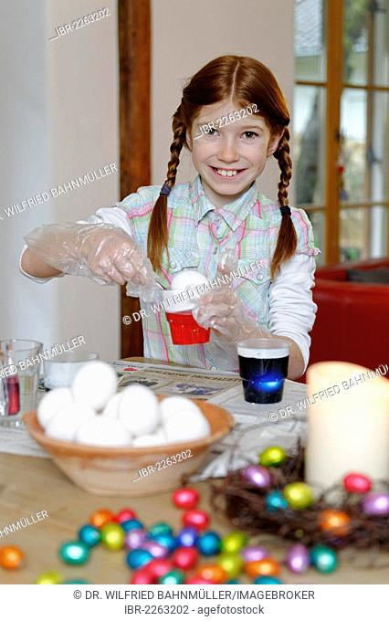 Child, girl colouring Easter eggs, Easter tradition