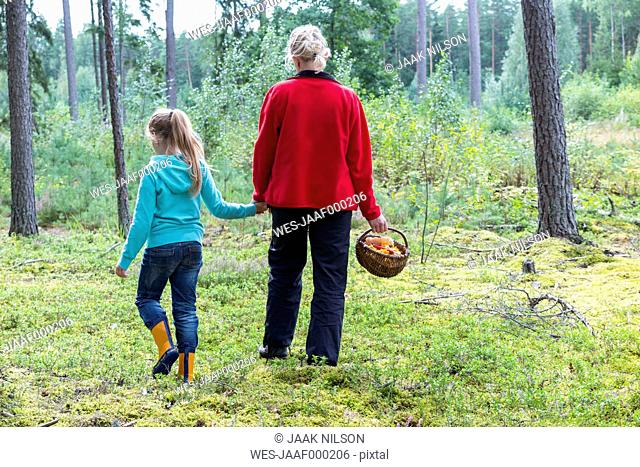 Estonia, mother and daughter with basket of mushrooms in a forest