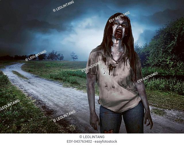 Scary zombie woman with wounds walking in the countryside road