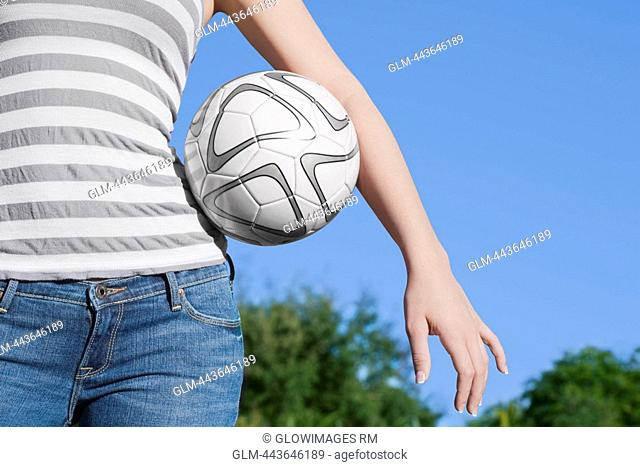 Mid section view of a teenage girl holding a soccer ball under her arm