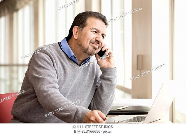 Hispanic businessman talking on cell phone near window