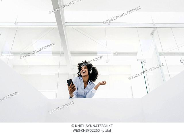 Happy young woman listening to music in office