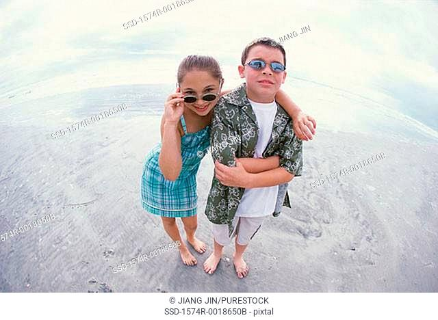 Portrait of a boy and a girl wearing sunglasses