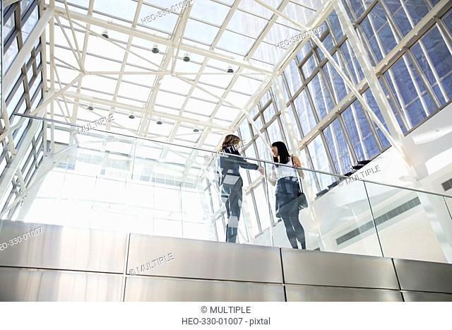 Businesswomen handshaking on atrium balcony