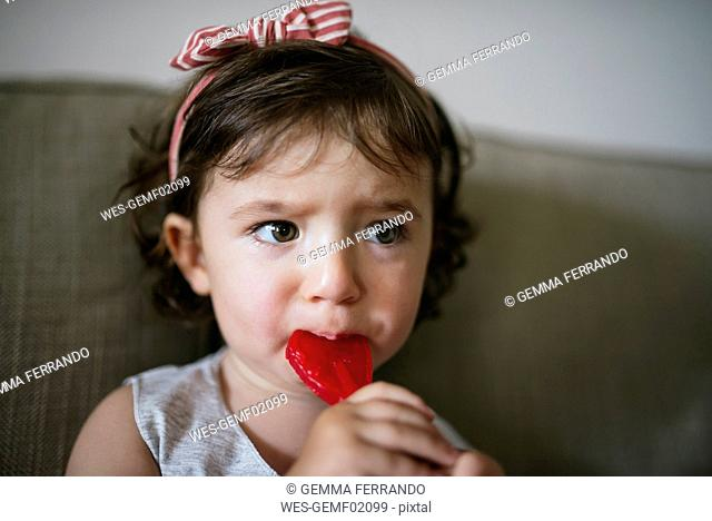 Cute baby girl eating a heart shaped lollipop at home