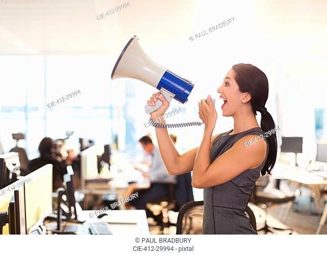 Exuberant businesswoman using megaphone in office