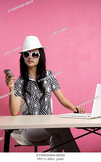 Young woman holding mobile phone, using laptop