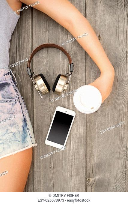 Beautiful young woman lying on the wooden floor with music headphones, smartphone and a take away coffee cup; view from above