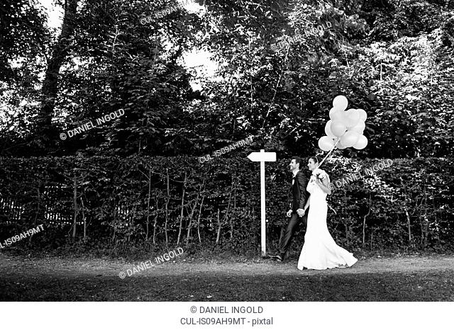 B&W image of mid adult bride and groom walking in garden