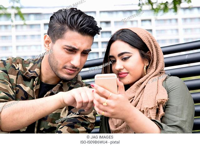 Young man and woman, sitting on park bench, looking at smartphone