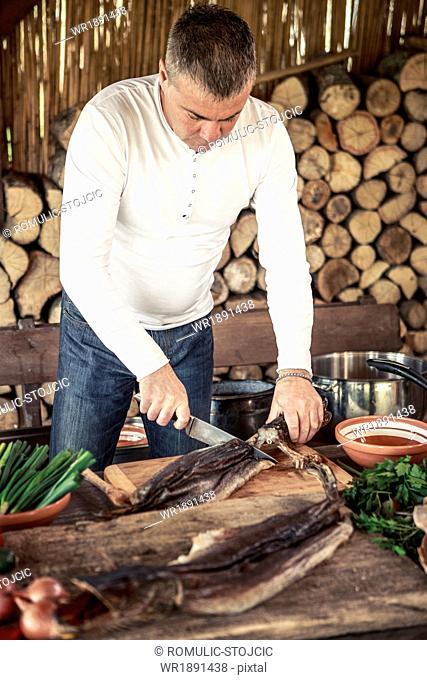 Man preparing fish on cutting board