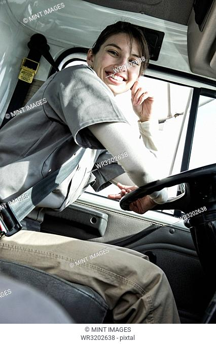 Portrait of a uniformed Caucasian female truck driver at the wheel of her truck at a distribution warehouse