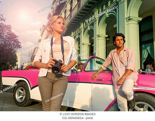 Young couple with vintage convertible taking photographs, Havana, Cuba