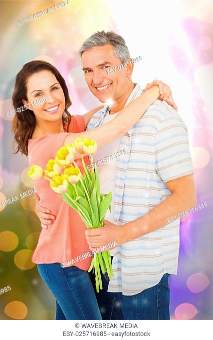Composite image of portrait of smiling couple with flowers bouquet