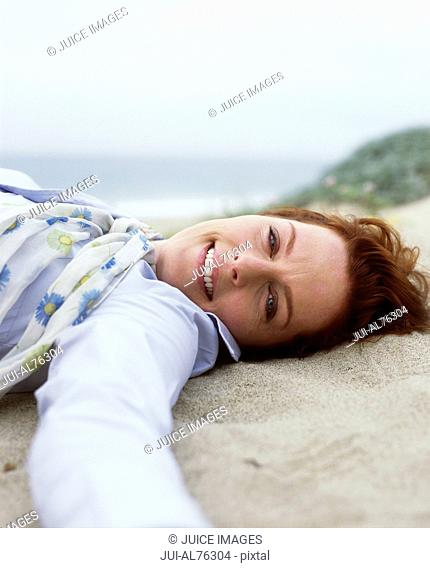 Portrait of a middle aged woman lying on the sand on a beach