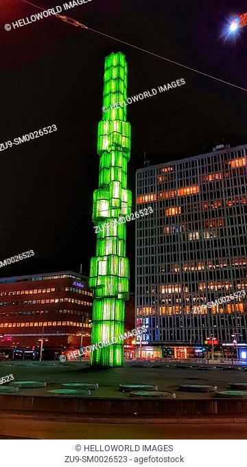 Glass Obelisk illuminated green at night, Sergels Torg, Stockholm, Sweden, Scandinavia. The 1974 obelisk is by Edvin Ohrstrom