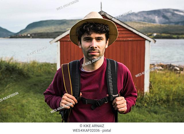 Young man with backpack exploring red barn in Northern Norway