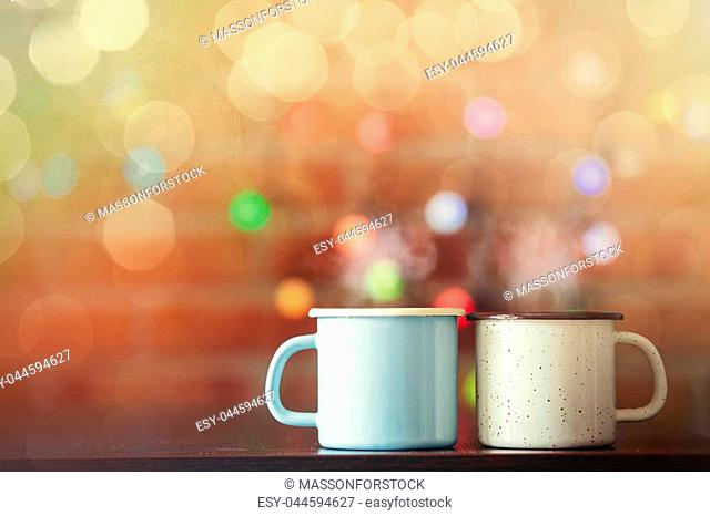 two Hot cups of coffee with fairy lights on background. Christmas season