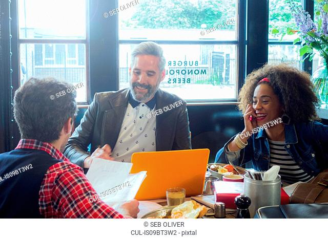 Friends at breakfast meeting in cafe, London, UK