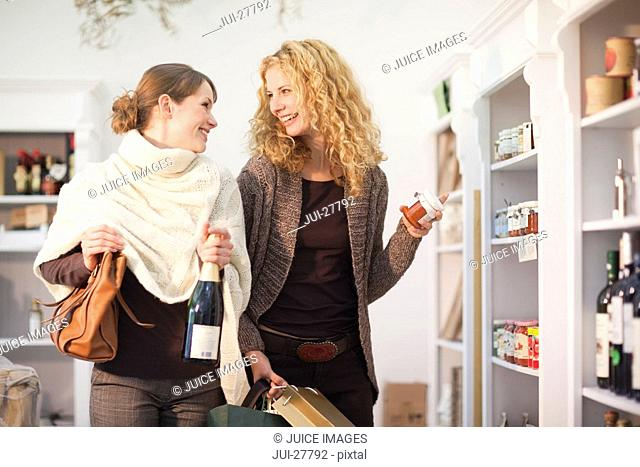 Two women shopping together for food and wine