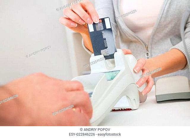 Sales person inserting card into scanner