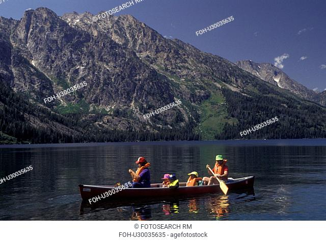 canoe, Grand Teton National Park, Lake Jenny, Grand Teton, Wyoming, Grand Teton Mountain, Rocky Mountains, A family paddles their canoe on Lake Jenny with a...