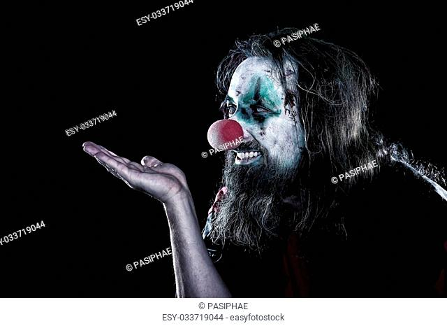 horror clown with ugly face looking to copyspace, black background, concept creepy theme party or halloween