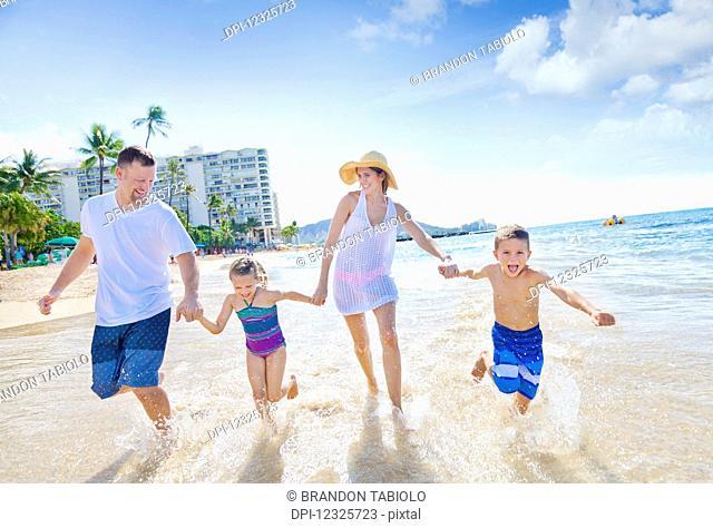 A family of four enjoying a summer vacation in Waikiki Beach; Honolulu, Oahu, Hawaii, United States of America