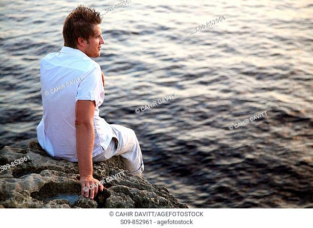 Tanned caucasian male with dark brown hair, age 25, wearing white shirt stares out on a sunset sea at Dwerja, on the island of Gozo, Malta