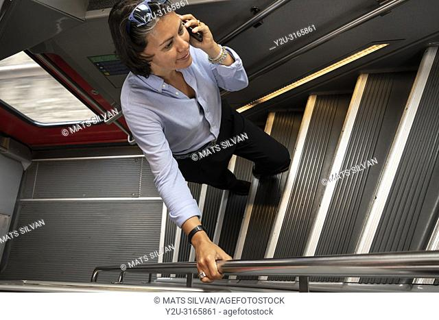 Woman Using Her Smartphone and Walking Up on a Staircase in First Class Train in Switzerland