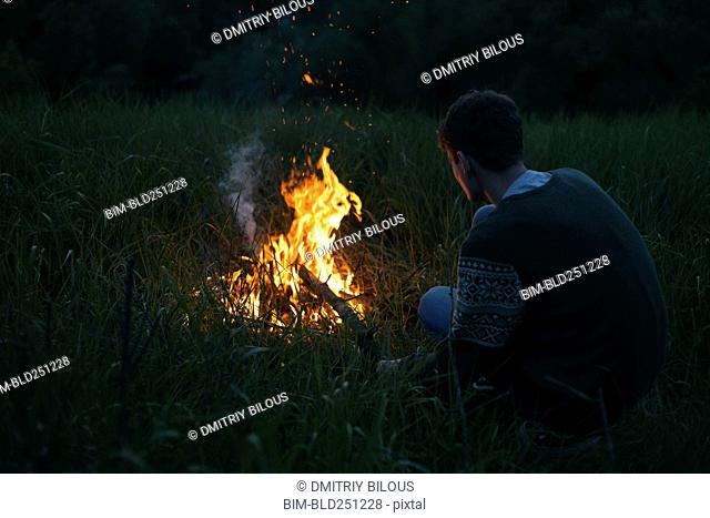 Caucasian man with campfire at night