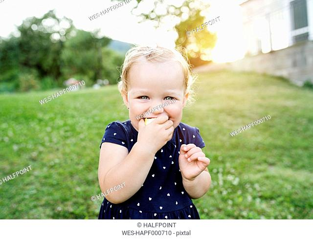 Portrait of little blond girl eating pastry