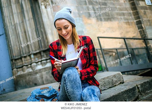 Spain, Barcelona, smiling young woman sitting on stairs writing in notebook