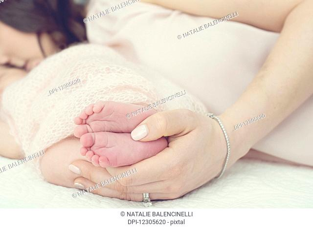 A mother laying on a bed with her hands holding a newborn baby's feet; Toronto, Ontario, Canada