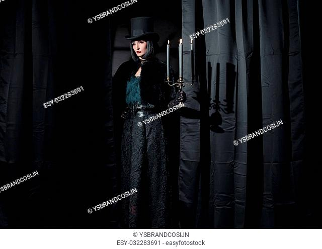 Witch gothic fashion woman wearing black cape and hat. Holding candlestick