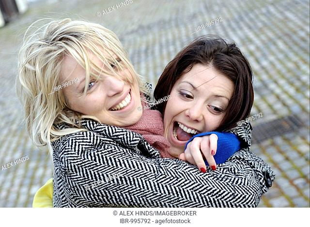 Two young women laughing and embracing with joy