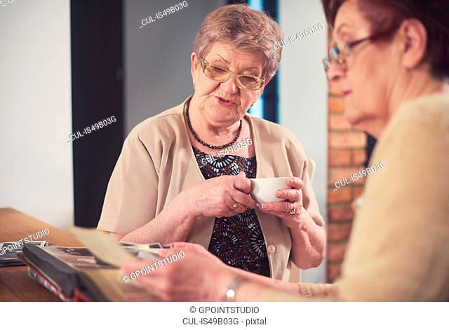 Two senior women looking at old photographs at table