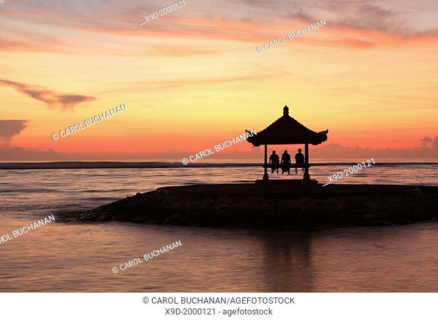 A three people in a Balinese Pagoda on the beach at Sanur. Taken at dawn. Bali, Indonesia