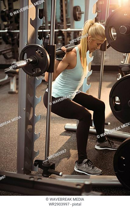 Fit woman exercising with smith machine