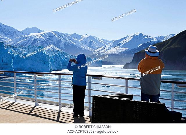 Cruise ship passengers snapping pictures of Hubbard Glacier and the St. Elias Mountain Range beyond. The channel of water between the couple is the entrance to...