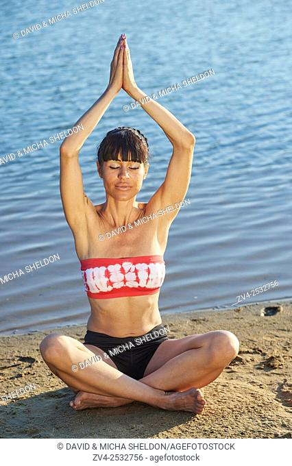 Young woman doing yoga on a beach next to a little lake
