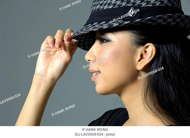 Close-up of a fashion model holding her hat