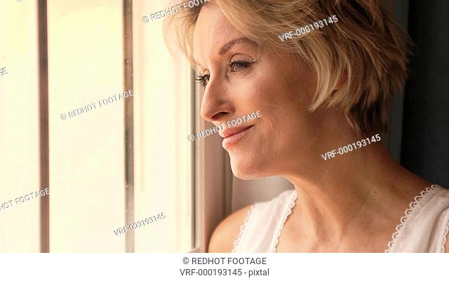 Dolly shot of woman in bedroom standing by window